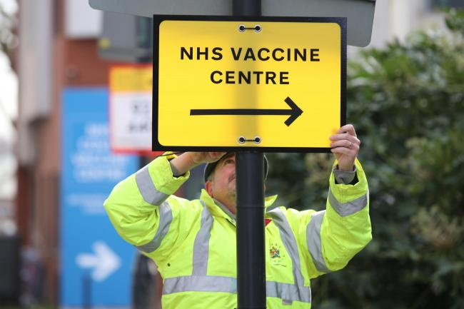 A Brent Council worker hangs a direction sign to the NHS Covid Vaccine Centre at the Olympic Office Centre, Wembley, north London, as ten further mass vaccination centres opened in England with more than a million over-80s invited to receive their