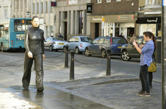 Man with cup and Walking Woman, statues outside Fenwick in Colchester High Street..